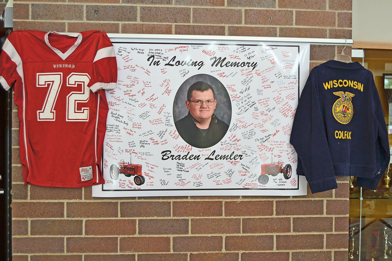 IN LOVING MEMORY —  A memorial has been set up in the lobby at Colfax High School for 16-year-old Braden Lemler. Dozens of students have written messages and signed their names on the poster with Braden's picture. Braden died in a car crash on county Highway M north of Colfax Friday afternoon on his way home from school. — Photo by LeAnn R. Ralph