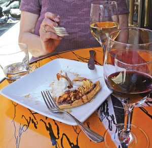 Paula enjoying a glass of French wine and apple pie alamode at a sidewalk café in Paris. The ice cream did not enhance the taste of the wine.