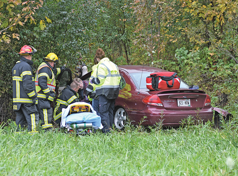 ONE-VEHICLE ACCIDENT — Glenwood City EMTs and firefighters work to extricate a Glenwood City man from his vehicle after he drove off Highway 128 just south of 170th Ave in the Town of Glenwood and into the ditch around 2:13 p.m. on Friday, October 5. Kevin P. Fraser, 60 of Glenwood City, was traveling south along Highway 128 in his 2005 Ford Taurus when he left the roadway and entered the west ditch, went up an embarkment over a driveway and took out a phone box before the car came to rest among a grove of small trees and bushes. Fraser was transported to West Wisconsin Health in Baldwin for elvaluation. Fraser was subsequently arrested for Operating a Motor Vehicle While Intoxicated and failure to keep his vehicle under control. —photo by Shawn DeWitt