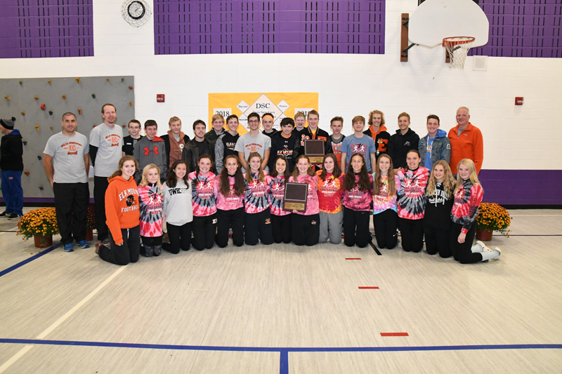 THE ELK MOUND boys' and girls' cross country teams claimed the 2018 Dunn-St. Croix Conference cross country championships in Boyceville Thursday, October 11. Members of the squads and their coaches hold the conference title plaques shortly after the Mounders' teams were announced the winners. —photo by Shawn DeWitt
