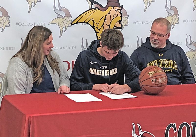 SIGNIN A LETTER OF INTENT — Colfax senior George Scharlau (center) signed his letter of intent last Tuesday afternoon, November 20, in front of the Colfax student body. Scharlau will join the Concordia-St. Paul basketball team next fall for the 2019-20 season. George was flanked by his parents Christina and John Scharlau at the signing ceremony.  —photo submitted