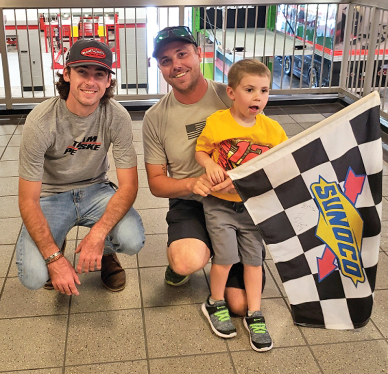 SPECIAL VISIT — Four-year-old Payton Brockmiller (right) and his father Ricky of Colfax, are pictured with NASCAR driver Ryan Blaney (left) at the Penske Racing Headquarters in Mooresville, North Carolina on Monday, October 1. Peyton and Ricky made a special visit to see Blaney after the Team Penske driver had awarded little Payton with the checkered flag he received after winning the Charlotte Roval at the Charlotte Motor Speedway the previous afternoon. After taking the win and checkered flag at the September 30 race, Blaney spotted Peyton in the grandstand, pointed at him and then climbed the wall to give him the flag. The Brcokmillers visited the Penske racing headquarter the next day, where they were given a tour and had Blaney autograph the checkered flag. Payton's grandmother, Julie Stansbury of Glenwood City, also accompanied the father-son pair to the race and Penske visit and took this photo.