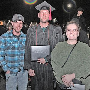 CELEBRRATING outside UW-Eau Claire's Zorn Arena after the CVTC Fall Commencement Tuesday, Dec. 18 are IT-Network Specialist graduate Darrin Schreiber of Menomonie, center, his son, A.J., and wife, Amy. —photo submitted