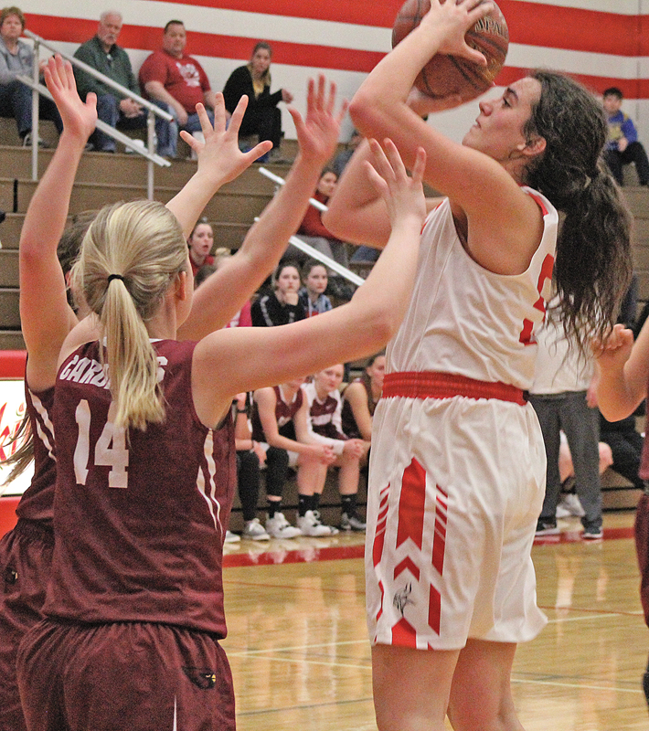 TRIPLE TEAMED— Emma Hurlburt (#54) sinks the two points after grabbing the rebound all while being guarded by Brenna Schreiber (#14), Morgan Rustad (#41), and one other Spring Valley defender. —photo by Amber Hayden