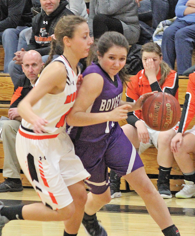 FIGHTING FOR THE LAY UP— Emma Ouellette (#11) fights off defender Alana Plaszcz (#13) on her way to the net for two. —photo by Amber Hayden
