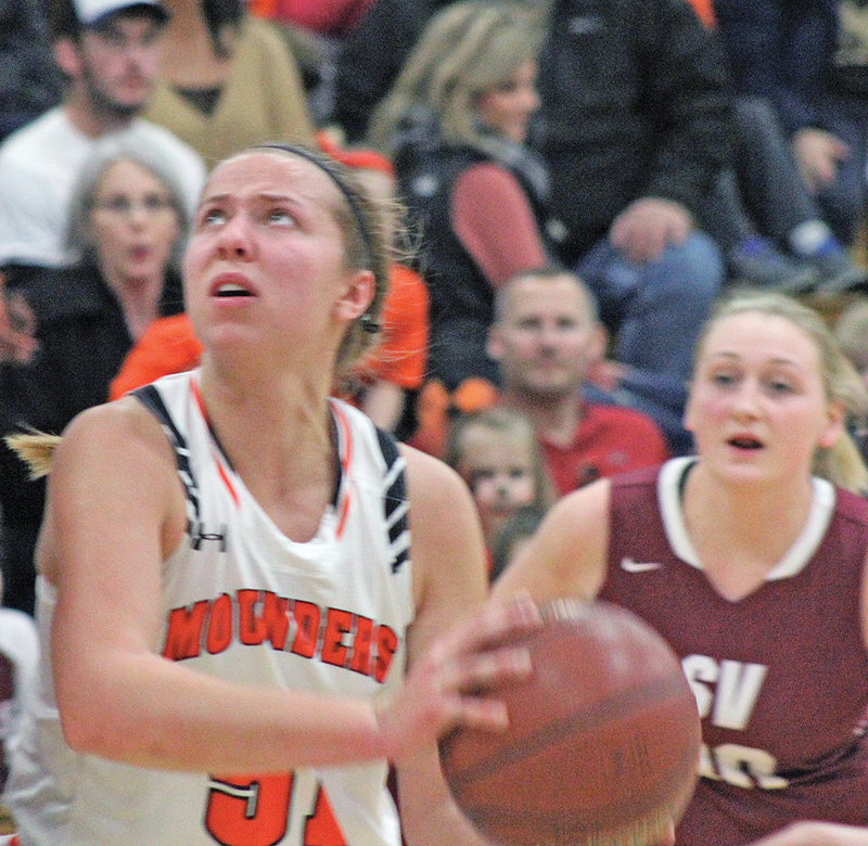 FROM UNDERNEATH - Morgan Radtke (#51) looks to grab two points from underneath while Brenna Schreiber (#14) attempts to get the block against the Elk Mound senior. Radtke finished her evening with 23 points for the Mounders. -photo by Amber Hayden