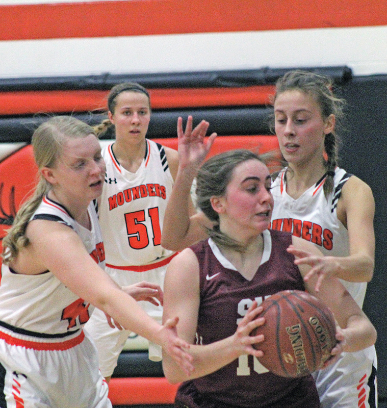 ATTEMPTING TO steal the ball from Erin Stanz (#10), teammates Brook Plaszcz (#11) and Sophie Cedarblade (#41) team up on defense for the Mounders during the 70-39 victory. -photo by Amber Hayden