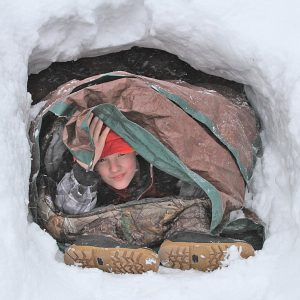 NATHAN NOSKER looked out of a snow cave members of Boy Scout Troop 243 built during a winter campout held February 22 and 23. —photo submitted