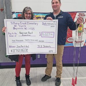 TCE MAKES DONATION — Corey Day, Tiffany Creek Elementary physical education teacher, handS off a check to Renee Davis of the American Heart Association. The month of January was a huge success for the fight against heart disease and stroke. Tiffany Creek Elementary students took on healthy heart challenges online, learned about nutrition, physical activity, being tobacco free and some awesome jump rope skills in physical education. Students also took part in raising money for the American Heart Association. Tiffany Creek Elementary had a goal of raising $3,500, which they crushed, collecting $5,027 in donations! —submitted photo