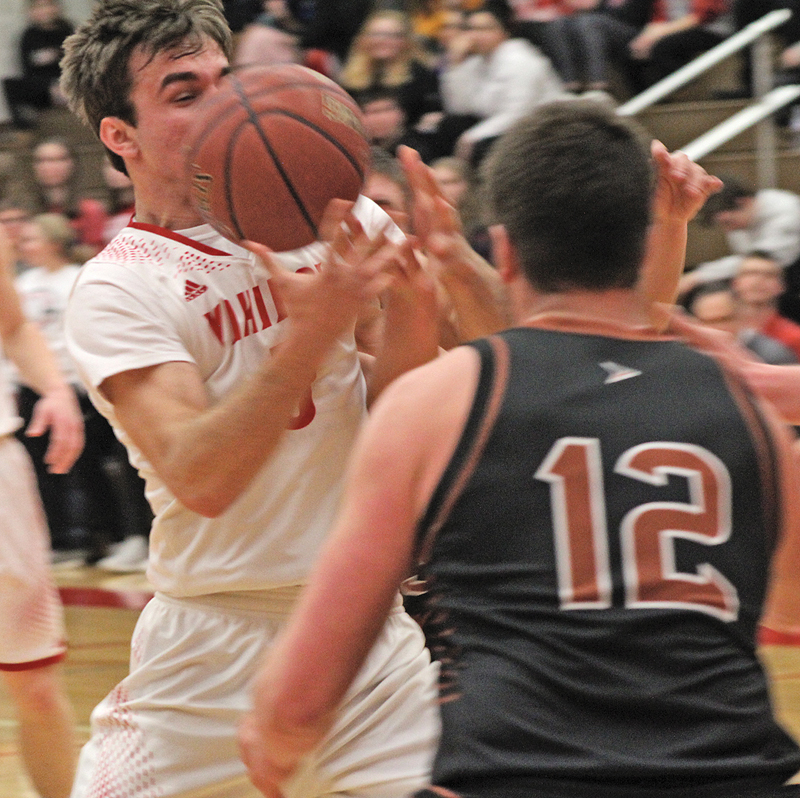 TAKING A ball to the face, Ben Thompson (#5), looks to hit the lay-up passed defender Bradley Sarauer (#12) during last Saturday night's contest. The Vikings went on to best the Blackhawks 47-44. —photo by Amber Hayden