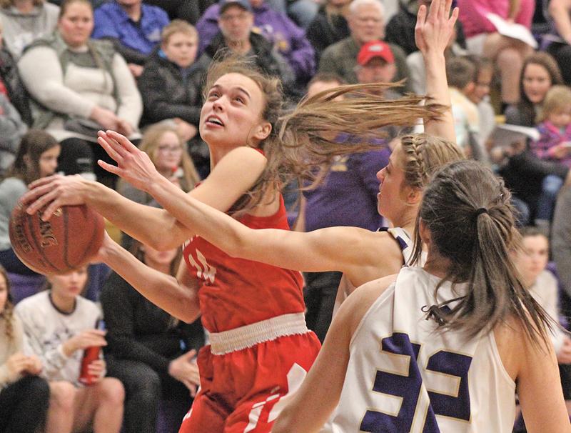 FROM UNDERNEATH— Kameri Meredith (#14) battles her way to the basket while fighting off defender Leah Sabelko (#22). —photo by Amber Hayden