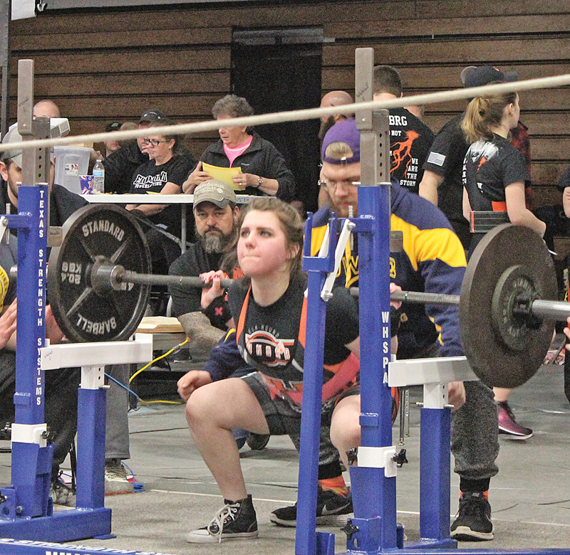 LIFTING HER first squat of the day, Bailey Gilbertson of Elk Mound began her set with a 150-pound squat before finishing up with a 175 pound squat in a February 9 regional meet in Elk Mound. Gilbertson is one of several qualifiers for the state meet in early March. —photo by Amber Hayden