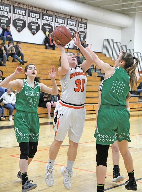 THE MOUNDERS' junior guard Hailey Blaskowski attempted this shot over Regis's Teryn Karlstad in a non-conference girls' basketball game in Elk Mound last Friday, February 1. The Ramblers defeated the Mounders 62-57 in overtime. —photo by Shawn DeWitt