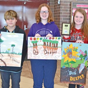 """CONTEST WINNERS — Three Colfax seventh graders placed first, second and third in the Dunn County Land and Water Conservation Division Grade 7 to 9 category of the wildlife poster contest sponsored by the National Association of Conservation Districts. The theme was """"Life in the Soil: Dig Deeper."""" First place winner Amy Wenzel, far right, also placed first in the West Central Land and Water Conservation Area competition, which was held on February 11 in Eau Claire. Amy's poster will go on to state competition in Lake Geneva March 13 to 15. Josephine Doerr, in the middle of photograph, placed second, and Brook Perry, far left, placed third. All together, there were 11 entries in the Grade 7 to 9 category from Colfax, and 31 entries from Colfax in all categories. —photo by LeAnn R. Ralph"""