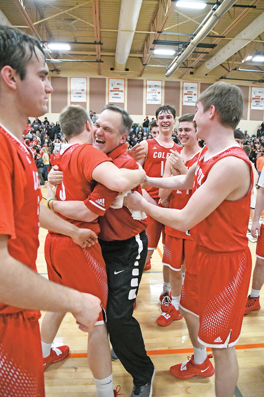 A TIME TO CELEBRATE — Jubilant assistant coach Tim Devine embrassed player Jackson Hellman following the Colfax Vikings 75-72 double-overtime, regional championship win over Webster last Saturday. —photo by Shawn DeWitt