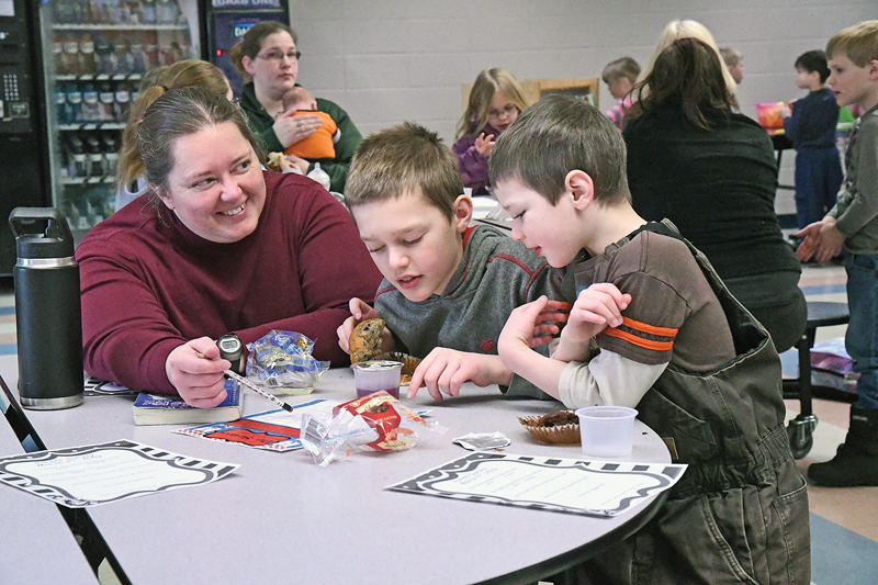 """MUFFINS, JUICE AND SOME DR. SEUSS — Tryn Gross along with her sons Garrett, a fifth grader, and Trevor, a kindergartener, read through a questionnaire during Glenwood City Elementary's annual kick-off to National Reading Month, """"Muffins and Juice with Dr. Suess"""" held last Friday morning, March 1 in the commons area. Nearly one hundred students and parents attended the event and enjoyed breakfast and reading Dr. Seuss books. —photo by Shawn DeWitt"""