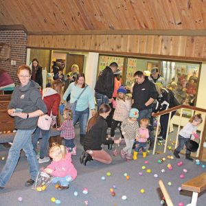 SCRAMBLE FOR EGGS — Several young egg hunters along with their parents, picked up colorful bounties inside Holy Cross Lutheran Church during the annual Glenwood City Community Easter Egg Hunt Saturday morning, April 13. The event had to be moved indoors after a spring storm dumped several inches of heavy wet snow throughout the area last Wednesday through Friday. —photo by Missy Klatt