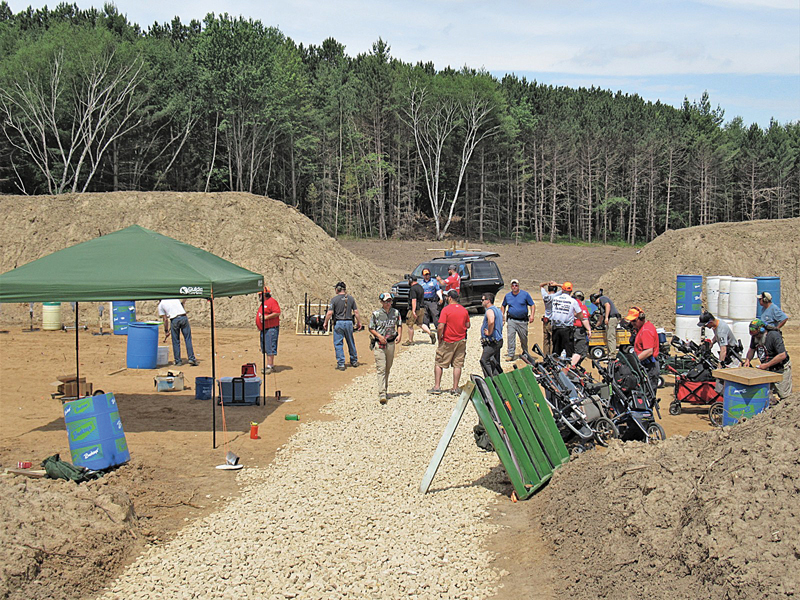 COMPETITORS ready their equipment between stages of fire June 9, in the newly constructed shooting bays at the Colfax/Dunn County Shooting Sports Complex.