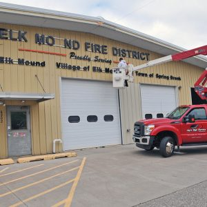 """FACE LIFT — The Elk Mound Fire Station as they begin removing the letters from the front of the building for the upcoming """"facelift"""". —photo by Carlton DeWitt"""