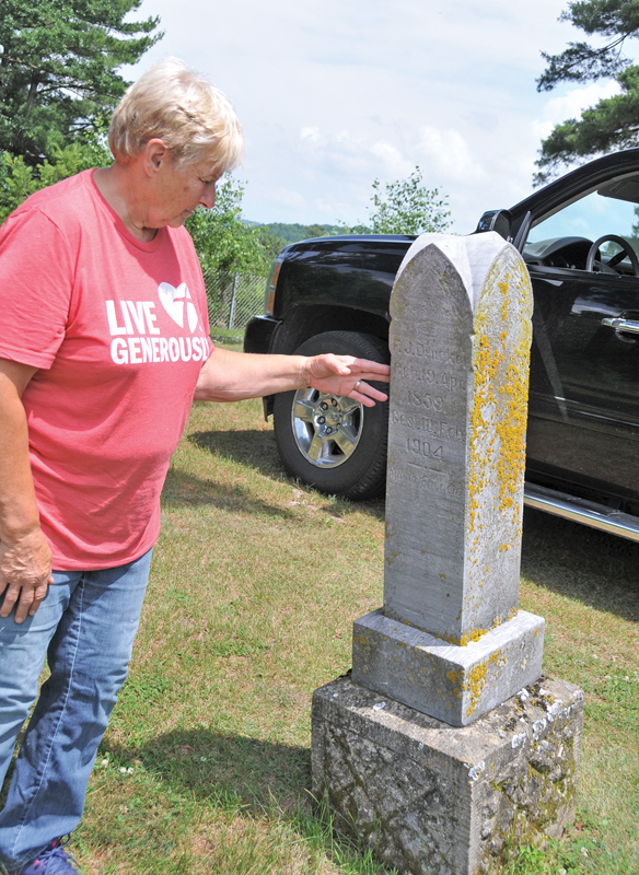 Lonna Borgert inspecting one of the several tombstones at Tiffany Cemetery