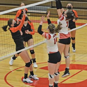 Madison Barstad and Bailey Bradford go up to block Elk Mounds Gracie Carlton