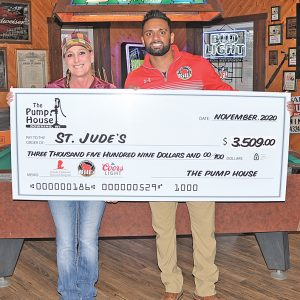 Laurie Stewart, left with Chris Steinbach of Bill's Distributing, hold up a large check representing $3,509 funds Stewart raised at the Pump House in Downing to benefit St. Jude in their annual fundraising effort. —photo by Shawn DeWitt