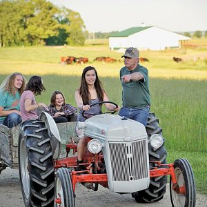 DOWN ON THE FARM — Dan Prestebak, retired Dunn County conservationist, shows students who visit his farm how to drive a tractor. — Photo submitted