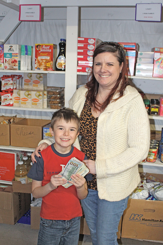 Kyle Gean and his mom Monica Nichols at the Knapp Food Pantry with the money Kyle earned baking and selling cupcakes for the pantry.