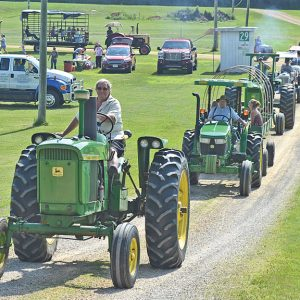LEADER OF THE PACK — Ken Maes (in front) of Glenwood City led the 8th annual St. Croix County Fair Tractor Caravan last Saturday morning, July 10 as it left the fairgrounds for a scenic 26-mile drive around the Glenwood City area. The annual caravan kicks off the St. Croix County Fair which runs July 14-18 this year. More than 30 tractors and over one hundred people participated in the event that went up Oak Street and visited residents at Glenhaven, Grand Oaks, and Havenwood on its way out of town. Maes took over coordinating and organizing the event which has becomea tradition that was orginally started by Dick and Gayle Sullwold. Dick Sullwold is piloting the tractor behind Maes. —photo by Carole Schurtz