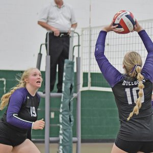 COMPETING IN a quad meet in Fall Creek last week, Harper Olson (#10) set the volleyball for her middle hitter, Libby Bygd (#19). —photo by Rochell Olson