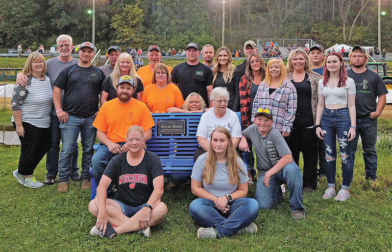 """A Bench Dedication in memory of the late Kevin Bonte was held Saturday evening, September 11 at the 10th Annual Glenwood City FFA Alumni Tractor and Truck Pull. The bench, which was made by Bob Dow, owner of Triple Valley Ironworks, who took over the trade from his grandfather Al """"Touser"""" Dow after his passing, will be placed into its permanent home at the St. Croix County Fairgrounds over the next few weeks once some accessories are added to the bench. Family members and friends sat on and gathered around the beautiful bench which was donated in memory of Kevin by the Glenwood City FFA Alumni. —photo submitted The bench was made by Bob Dow, owner of Triple Valley Ironworks, who took over the trade from his grandpa Touser after his passing. The beautiful bench was donated in memory of Kevin by the GC FFA Alumni!"""