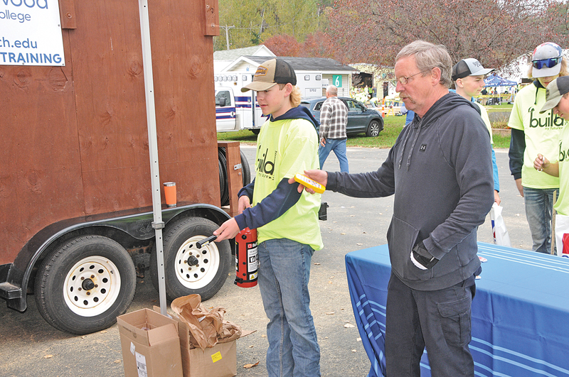 """MIKE SPENCER of the Northwood Vocational School out of New Richmond, demonstrates the proper use of a handheld fire extinguisher to Brady Berg, a Colfax High School Student, at the """"Build My Future Wisconsin"""" educational program held at Glenwood City last week."""