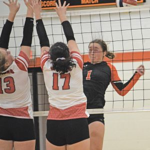 BLOCKED — Jada Anderson (#13) and Jeanette Hydukovich (#17) successfully blocked a kill attempt by Elk Mound's McKenna Diermeier in the game played in Elk Mound October 7. —photo by Marlys Kruger